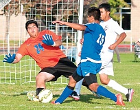 LON AUSTIN/CENTRAL OREGONIAN - Crook County goalkeeper Christian Nunez makes a stop on a shot by Madras forward Miguel Alonso. Crook County defender Christian Hernandez is also involved in the play.