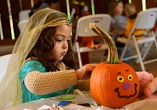 SPOKESMAN PHOTO: VERN UYETAKE - Chloe Elbitar, 5, of Wilsonville concentrates on decorating her pumpkin at Saturdays Harvest Festival at Memorial Park.