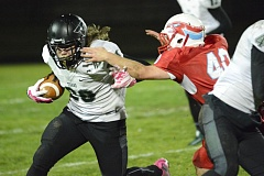 OUTLOOK PHOTO: DAVID BALL - Tigard running back Peyton Olson looks to escape Centennial's Ryan Payne during the Tigers' 34-22 playoff win Friday night.