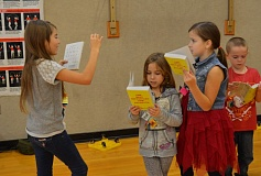 SPOTTLIGHT PHOTO: NICOLE THILL - Third-graders Sophia Willett, Lileigh Baer and Hailey Pierson leaf through the dictionaries they received. The students began looking through the books while lined up in the gym before going back to class.