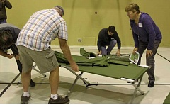 TERRI POET - Mayor Deborah Rogge, right, helps set up cots in an emergency shelter at a recent Molalla Disaster Ready Event where community leaders got 'a peak behind the disaster curtain.'