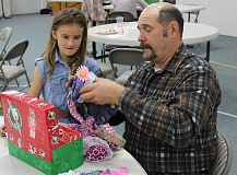 JASON CHANEY - Lee Ashcraft, right, helps Moriah Riley fill a shoebox on Sunday afternoon at Calvary Baptist as part of this year's Operation Christmas Child.