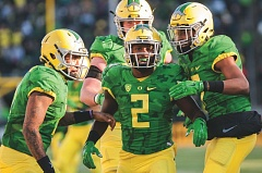 TRIBUNE PHOTO: JOSH KULLA - Bralon Addison (center) celebrates another score with Vernon Adams Jr. (left) and Darren Carrington. Addison scored four touchdowns for the Oregon Ducks in their 52-42 win over Oregon State on Friday.