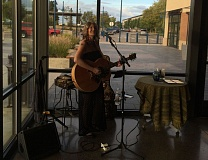 PHOTO COURTESY OF THE SHERWOOD CENTER FOR THE ARTS - Singer-songwriter Gayle Ritt performs at the inaugural Art Walk in Sherwood this September, with the streetscape of Southwest Pine Street in the background.