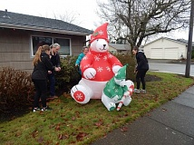 BARBARA SHERMAN - In King City during the Tigard High School Key Club's annual project to help seniors decorate their homes for the holidays, (from left) THS sophomore Sara Rumbaugh, club advisor Fred Holtz, homeowner Barbara Lee and THS junior Alexys Krogh work to get Lee's bear inflated and anchored down.