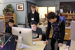 SUBMITTED PHOTO - Wilsonville High School student Tyler Greco, far right, helps Joshua Budiao during an Hour of Code event Dec. 9.