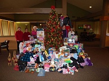 BARBARA SHERMAN - With two days to go for gifts to be turned in, a large pile of presents had been collected under the Summerfield Clubhouse tree ; from left are organizer Kathy Peper, Janis Phannenstiel, Yvonne Welch, Jean Madrid and  Suzanne Whisler,.