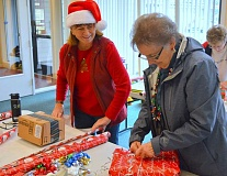 SPOKESMAN PHOTO: JAKE BARTMAN - Charbonneau Country Club Board Member Kathy Harp, left, and Faye Turner volunteer to wrap gifts donated to two Wilsonville families in need by Charbonneau residents.