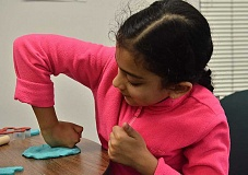REVIEW PHOTO: VERN UYETAKE - Drishti Singh, 7, has fun creating a work of art with Play-Doh at the Parks & Recreation Department's indoor playground at Palisades.