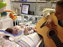 A newborn baby is rapt with attention as a musical therapist sings and plays the guitar. Scientific evidence shows music therapy greatly aids premature babies.