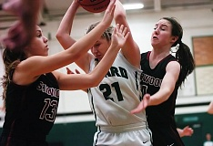 DAN BROOD - Tigard junior wing Kylie Warren (center) tries to keep the ball away from Sherwood junior Cami Reuter (left) and freshman Teagan McNamee in the fourth quarter of Friday's game.