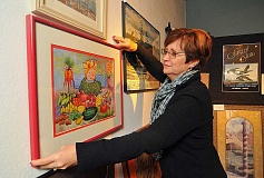 REVIEW PHOTO: VERN UYETAKE - Debi Bradway helps hang donated pieces at the Arts Councils ArtMart, which continues through the end of the month at the 510 Museum and ARTSpace in downtown Lake Oswego.