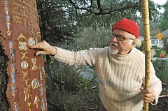 STAFF PHOTOS: VERN UYETAKE  - Lake Oswego artist Roger A. Long points out a portion of his Living Script work at the Living Garden on Evergreen Road in Lake Oswego.