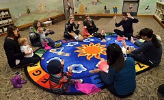 REVIEW PHOTO: VERN UYETAKE - Are we having fun yet? The answer is a big 'Yes' from the babies and their mothers who gather around a colorful rug every week for Baby Story Time at the Lake Oswego Public Library.
