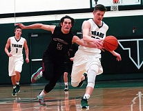 DAN BROOD - Sherwood junior Jacob Maddox (5) and Tigard sophomore Jake Estep battle for a loose ball in Friday's game.