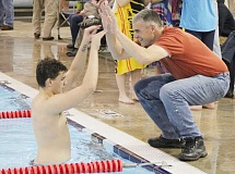 JEFF WILSON/THE PIONEER - Madras swimmer Garrett Webb, left, celebrates breaking the Madras High school record in the 50-yard freestyle with his father Steven Webb Thursday at the Madras Aquatic Center. The younger Webb, who had been chipping away at the record all year, swam a 23.24 to top the mark by a full half-second.