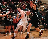 DAN BROOD - Tualatin senior Nathan Senger (left) looks to drive past Lake Oswego senior Drew Todd in Tuesday's game.