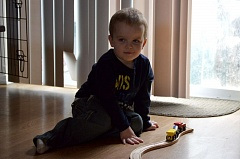 SPOTLIGHT PHOTO: NICOLE THILL - Clayton Moore, a 3-year-old in St. Helens, plays with a train set on the family's living room floor. Laura Moore, Clayton's mother, is planning a fundraiser next week to help pay for medical bills the family is facing.