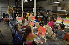 SPOTLIGHT PHOTO: NICOLE THILL - Kim Henrie, an art teacher at Sauvie Island Academy, explains what students should paint on their canvases first. The 24 students who signed up for the art night all painted a sunrise behind the Sauvie Island Bridge, with each piece reflecting each student's style.