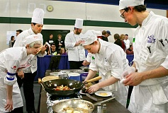 SUBMITTED - A judge at the Oregon ProStart Championships, along with Newberg senior Katherine Shephard, observes NHS culinary team members Sydney Roesli (center) and Tim Forbes in action at the cooking competition Feb. 27.