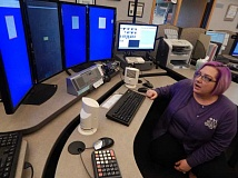 BARBARA SHERMAN - WCCCA call taker/lead dispatcher Mary VanCleve sits at a 9-1-1 computer station to show guests from King City how the system works.