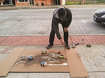 COURTESY PHOTO: VALERIE OTANI - Artist Corey Lunn of Portland works on stenciling rain art on a Main Street sidewalk. His public art installation, Oasis Gargoyles are visible only when it rains.