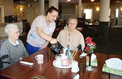 HOLLY SCHOLZ - Nicole Acord, a cook at Regency Village at Prineville, serves coffee to residents Dorothy Smith (left) and Lorette Jacobsen. The local assisted living facility recently changed its name from Ochoco Village Assisted Living and was recognized in the top 1 percent of the nation's senior living facilities.