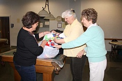HOLLY SCHOLZ/CENTRAL OREGONIAN - Members of the Saturday Stitchers pack quilts that were donated to five local community organizations that serve the less fortunate. From left, Caran Clinard, Kathy Vaughan and Sandy Stearns.