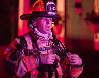 OUTLOOK PHOTO: JOSH KULLA - A Gresham firefighter looks weary after fighting a residential blaze at a home on Southeast Hogan Road.