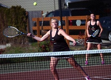 DAN BROOD - Sherwood High School senior Meghan Howard (left), in front of junior Sierra McCaulley, gets ready to hit a shot at the net during last week's match with Wilsonville. Howard and McCaulley won their No. 1 doubles match in three sets.