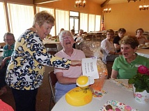 BARBARA SHERMAN - At the Summerfield Women's Golf Club winter closing luncheon, Carole Krueger hands Marilyn Katz the prize for most balls in the water while Robin Nash enjoys the moment; however, moments later, it was revealed that Katz had not won the prize for the second year in a row after all.