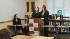 SUBMITTED PHOTO - Lauren Anderson (left) and Kelsey Talbot stand at a lectern to argue their position during a recent competition. The two took second place in nationals in the Virtual Supreme Court Competition. Seated near Talbot and Anderson are Sophie Croome (left) and Mckenna Murray, who were honored as semifinalists in the competition.