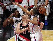 TRIBUNE PHOTO: KIRBY LEE - The Los Angeles Clippers sandwich Trail Blazers center Chris Kaman during Game 2.