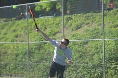 SPOKESMAN PHOTO: COREY BUCHANAN - Wilsonville doubles player Daryl Wainwright hits a serve against Sandy.
