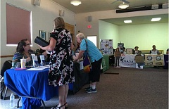 SUBMITTED PHOTO - Ladies pick up information from some of the many booths at the Volunteer Fair in Madras.