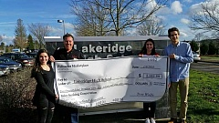 SUBMITTED PHOTO - Troy Wolfe, Palisades Marketplace's store director, hands a check to Lakeridge students. From left: sophomore Mallory Spring, freshman Talia Milionis and senior Simon Homedes.