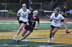 MATTHEW SHERMAN - Lauren Gilbert looks for room on a breakaway during Tuesday's game against West Linn. Gilbert scored five of the Lakers' 10 goals and also led the team in draw captures.
