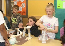 SUSAN MATHENY/MADRAS PIONEER - Culver third-graders Cole Rahi, left, Ryleigh Daniels and Toni Morales show water slides and a merry-go-round they made out of egg cartons, paper towel rolls and paper plates, for their town's park.