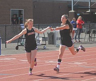 JEFF WILSON/THE PIONEER - Culver's Jessica Johnson, left, takes the baton from Hannah Lewis during the 1,600-meter relay Saturday at the Madras Invitational.