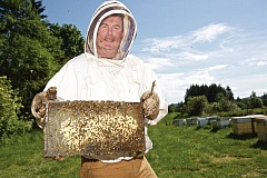 TIMES PHOTO: JAIME VALDEZ - Beekeeper Ron Stark who runs T Bee S, a bee pollination company in Sherwood, holds a frame from his beehive located at Rowell Brothers Berry Farm in Scholls. Photo by Jaime Valdez