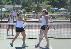 SPOKESMAN PHOTO: COREY BUCHANAN - Wilsonville doubles players Hanna Heilig (left) and Madi Wardle slap hands during the district tournament.