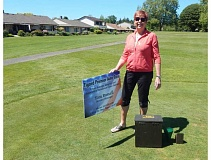 BARBARA SHERMAN - Sandy Brewer, chair of this year's Summerfield Women's Golf Club charity fundraiser, shows a sign like ones that tee box sponsors can purchase for display during the upcoming charity golf tournament.