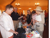 BARBARA SHERMAN - Following a presentation by the American Red Cross at the Summerfield Clubhouse about disaster preparedness, Jan Meek (left) watches over a table of sample items that should be put in a kit.