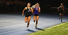 TIMES PHOTO: MATT SINGLEDECKER - Jesuit's Sydney Collins outruns Sunsets Nicole Griffiths to the tape during the final leg of the 4X400 relay at the Metro League district championship at Aloha High School.