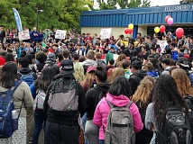 NEWS-TIMES PHOTO: KATHY FULLER - The peaceful, predominantly Latino crowd at Hillsboro High School took three laps around the parking lot, holding signs, flags and balloons.