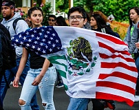 NEWS-TIMES PHOTOS: TRAVIS LOOSE - Demonstrators carried American flags, Mexican flags and this specially crafted flag that combines the two, showing their love for both the country their families came from and the country they now call home.