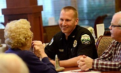 REVIEW PHOTO: VERN UYETAKE - Lake Oswego Fire Department Assistant Chief David Morris visits with Gloria Wetmore (left) and Ron Wetmore during breakfast Friday at The Stafford Retirement Community.