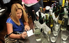 REVIEW PHOTO: VERN UYETAKE - Danielle Miller, in her second year on the School Advisory Committee with Lake Oswego Junior High, writes a note to Robert Caplinger on a wine tag. Attendees all were welcome to pen special notes.