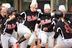 THE OUTLOOK: DAVID BALL - Mt. Hoods Tiara Champ leads the charge out of the dugout to embrace teammate Rachel Rutledge, 8, after she came home with the winning run in the eighth inning Sunday.