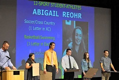 SETH GORDON - (From left to right) Jacqueline Baca, Jay Byers, Ben Fox, Hayley Hensley and Jakob Holter take the stage June 1 at the NHS all-sports dessert as recipients of Newberg High School's 12-sport-athlete award, which recognizes seniors who have played a sport in each season for all four years of their career. Also receiving the honor were Chase Pothier, Caleb Rauch and Abby Reohr.